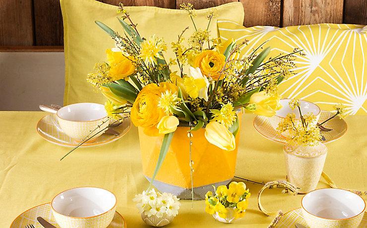 Tischdekoration in frischen Gelb- und Rottönen