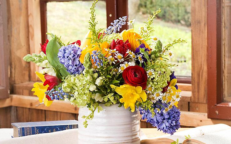 Üppiges Gebinde am Fensterbrett aus Narzissen, Tulpen, Ranunkeln, Hyazinthen, Goldrute, Schneeball und Löwenmaul.